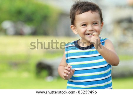 Happy little boy smiling while running in green nature