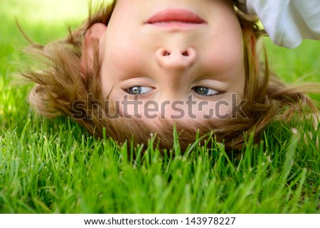 Happy little boy standing upside down on green grass in spring park