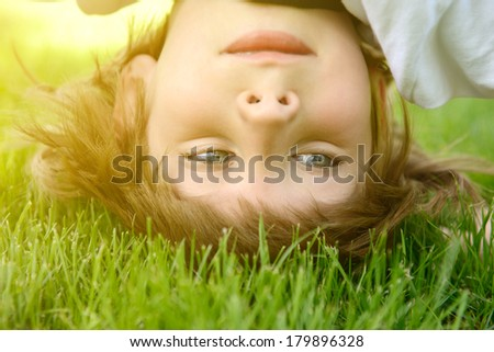 Happy little boy standing upside down on green grass in spring park, toned