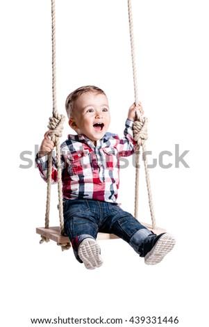 happy little boy swinging on a wooden swing