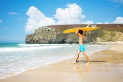 Happy little boy walk with orange surfboard over his head to the sea waves on the beach