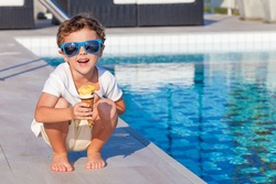 happy little boy with ice cream sitting near a swimming pool at the day time.