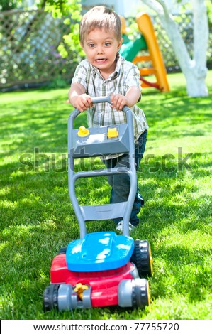 Happy little boy with lawn mower in the garden