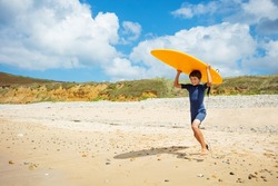 Happy little boy with surfboard run to the sea on the sand beach
