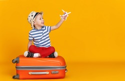 Happy little boy with toy plane sitting crossed legged  against yellow background