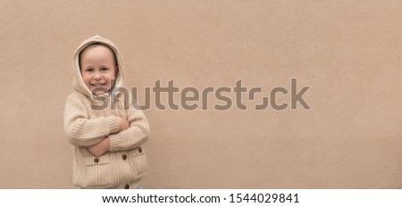 Happy little boy 3-5 years old, warm beige sweater with hood, free space text. Emotions of joy, happiness, delight pleasure, new year holiday. Background wall, having fun playing joyful and smiling