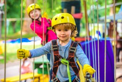 Happy little boyn calling while climbing high tree and ropes. Eco Resort Activities. Go Ape Adventure. Roping park. Toddler age. Hiking in the rope park boy in safety equipment