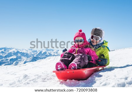 Happy little brother and cute sister enjoying sleigh ride. Smiling children sitting on the sled. Children play with bobsled outdoors in snow. Winter vacation concept. ストックフォト ©