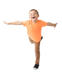 HAPPY LITTLE CAREFREE BOY SMILING AND HOLDING BALANCE STANDING ON ONE LEG WITH WAVING HANDS ISOLATED ON WHITE BACKGROUND