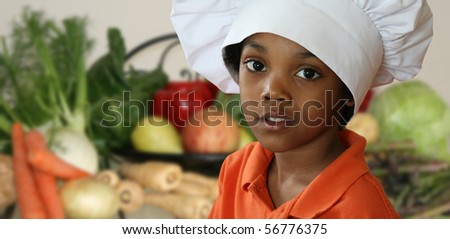 Happy little chef standing in front of a variety of vegetables.