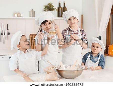 happy little chefs preparing dough in the kitchen - stock photo