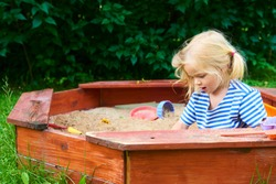Happy little child, adorable blond child  girl having fun playing outdoors in the garden with plastic toys sitting in blue sand box on a sunny summer day