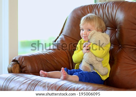 Happy little child, adorable toddler girl with blonde curly hair playing with her teddy bear sitting indoors on brown leather sofa in bright room with big garden view window