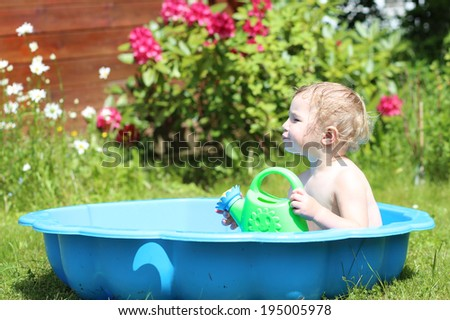 Happy little child, cute blonde toddler girl splashing in small plastic baby bath outdoors in beautiful big garden at the backyard of the house on a hot sunny summer day