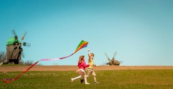 Happy little child girl and boy in front of windmills playing kite. Children running on the field. Renewable and green energy. Kids playing near a wind turbine. New generation