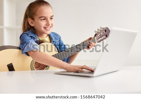 Happy little child in denim shirt learning to play guitar while watching lessons at laptop and smiling at home ストックフォト ©