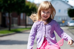 Happy little child running towards the camera jumping. Smiling cheerful active girl with dispelled flying hair moving fast towards the camera, closeup, portrait, small city in the back, outdoors scene