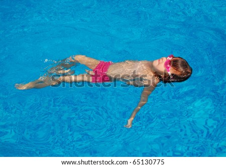 Happy little child swimming on her back in pool. Active girl swims and having fun. Child sport on summer vacation