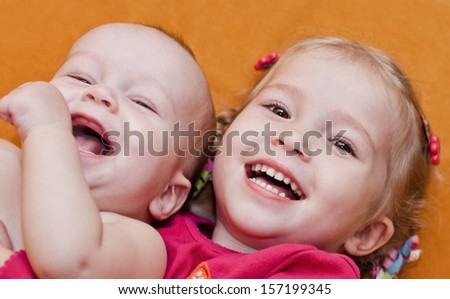 happy little children brother and sister hugging lying on an orange background