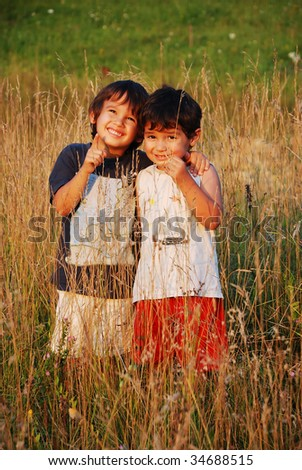 Happy little children in grass on meadow