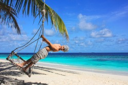 Happy little cute eight year old boy  is swinging on coconut palm tree seesaw on exotic tropical beach on background. Beach seesaw under palm trees. Play, relaxing.Summer Leisure activities.