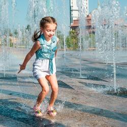 happy little cute girl having fun in splashes a fountain