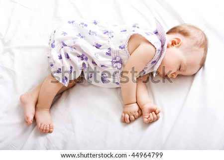 Happy little cute girl sleeping on the bed
