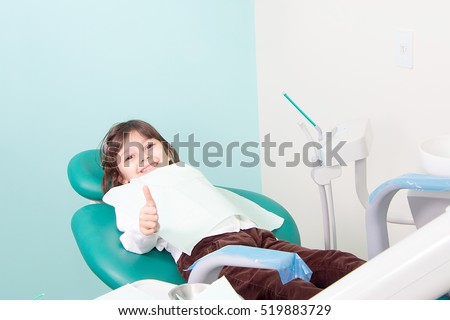 Happy little cute girl smiling and showing OK sign at dental clinic