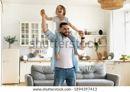 Happy little daughter sitting on father neck piggybacking playing active game at home. Smiling dad holding cute girl with arms outstretched carrying on back. Family spending weekend together.
