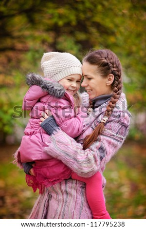 happy little girl and her mother in the autumn park