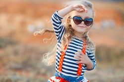 happy little girl at the seaside in the summer.Adorable little girl at beach during summer vacation. Happy baby with sunglasses by the sea or ocean
