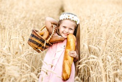 Happy little girl child in wheat cereal field in summer. Children with bread. Little girl in cereal field. Baby girl on field of wheat with bread