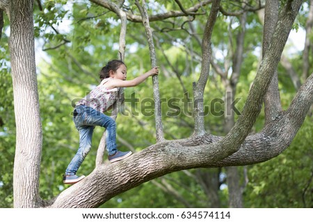 Happy Little Girl climbing a tree