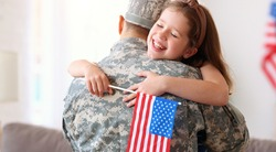 Happy little girl daughter with American flag hugging father in military uniform came back from US army, rear view of dad male soldier reunited  reunited with family at home