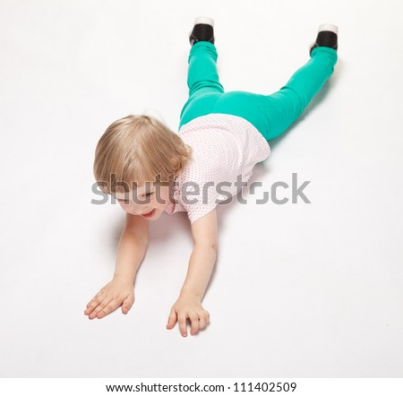 Happy little girl doing gymnastics lying on the floor on white background