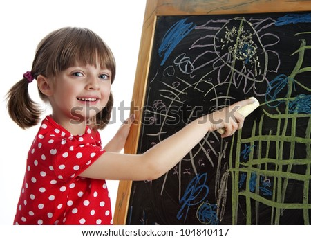happy little girl drawing picture with chalks on a black board