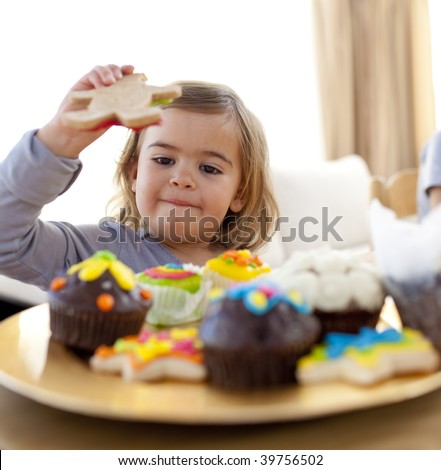 Happy little girl eating colorful confectionery at home