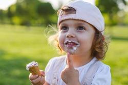 Happy little girl eating ice cream