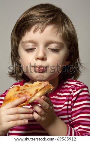 happy little girl eating slice of pizza