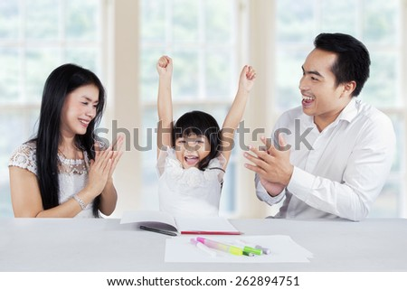 Happy little girl finishing her homework and get applause from her parents at home