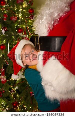 Happy little girl giving santa claus a big hug