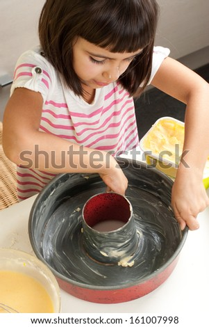 Happy little girl greasing a mold with hand to bake a cake