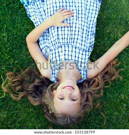 happy little girl having fun lying on green grass