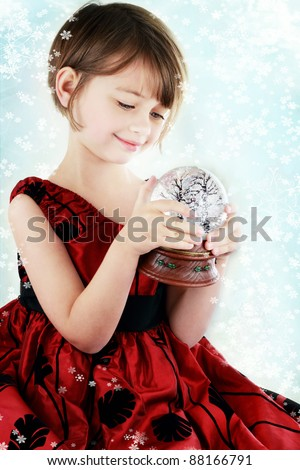 Happy little girl holding a Christmas snow globe. Shallow depth of field with selective focus on snowglobe in her hands.