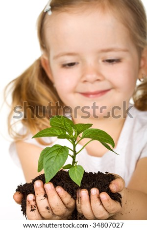 Happy little girl holding a vigorous new plant with soil - isolated, focus on the plant
