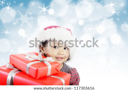 Happy little girl holding couple of Christmas gifts wrapped with red paper and gold ribbon on background of defocused blue lights