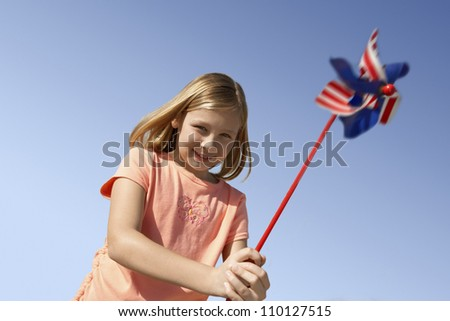 Happy little girl holding pinwheel against clear sky