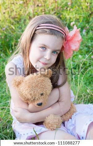 Happy little girl hugging a teddy bear  against summer nature.