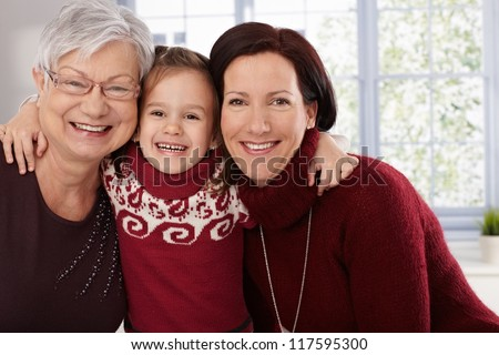 Happy little girl hugging grandmother and mother, all smiling.