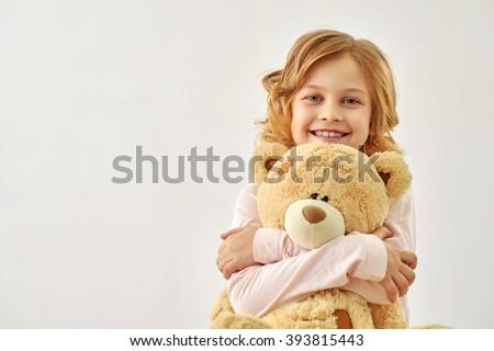 Happy little girl huging bear